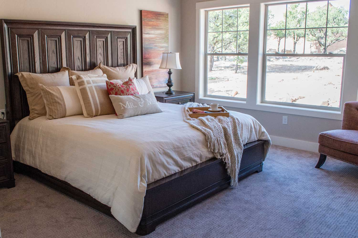master bedroom with king size bed, side tables, and window view into backyard