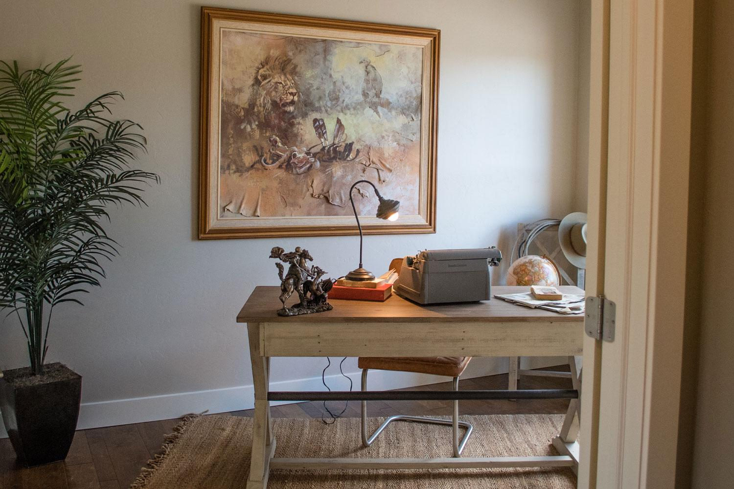 office room with large painting on the wall, one small desk and chair and desk lamp, area rug on the floor