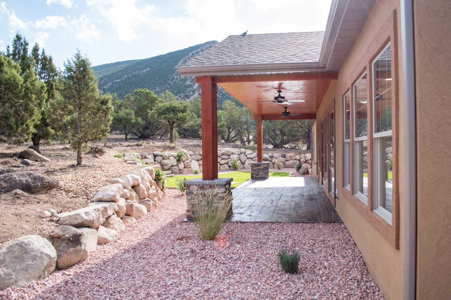 back patio exterior, small red rock gravel, smooth stamped dark brown concrete, rock retaining wall and pine trees, blue sky with light clouds