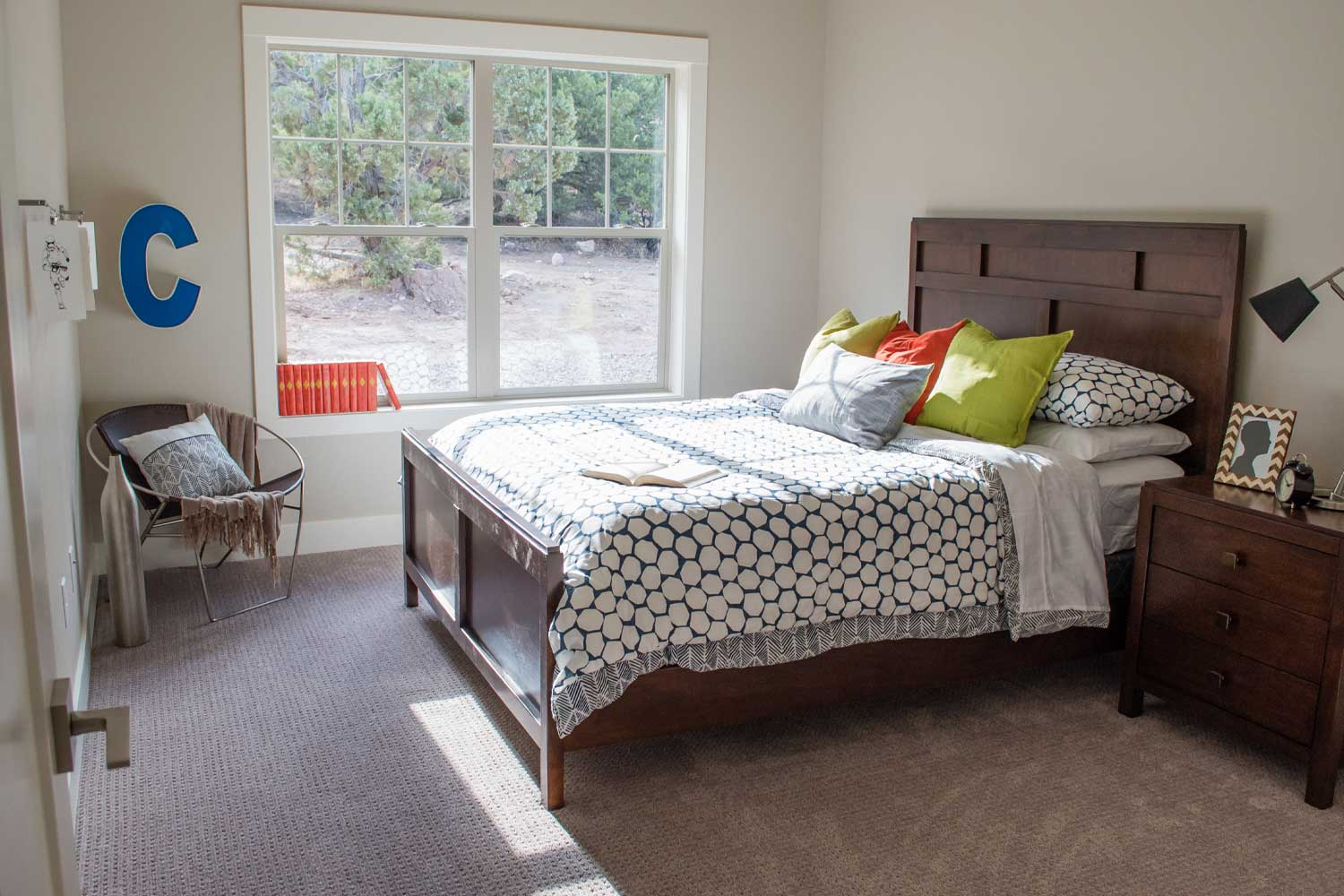spare room with one queen size bed, dark wood bedframe, bright natural light come from main window that looks out into backyard