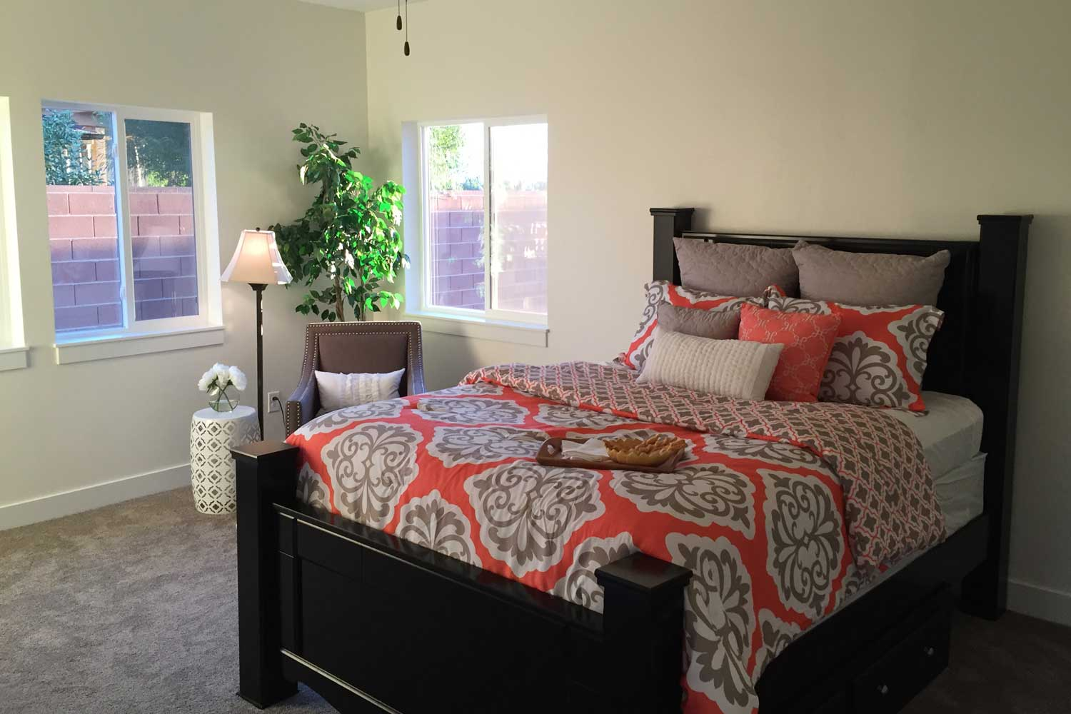 bedroom with beige carpet, queen bed and orange colored bedspread with sitting chair in the corner