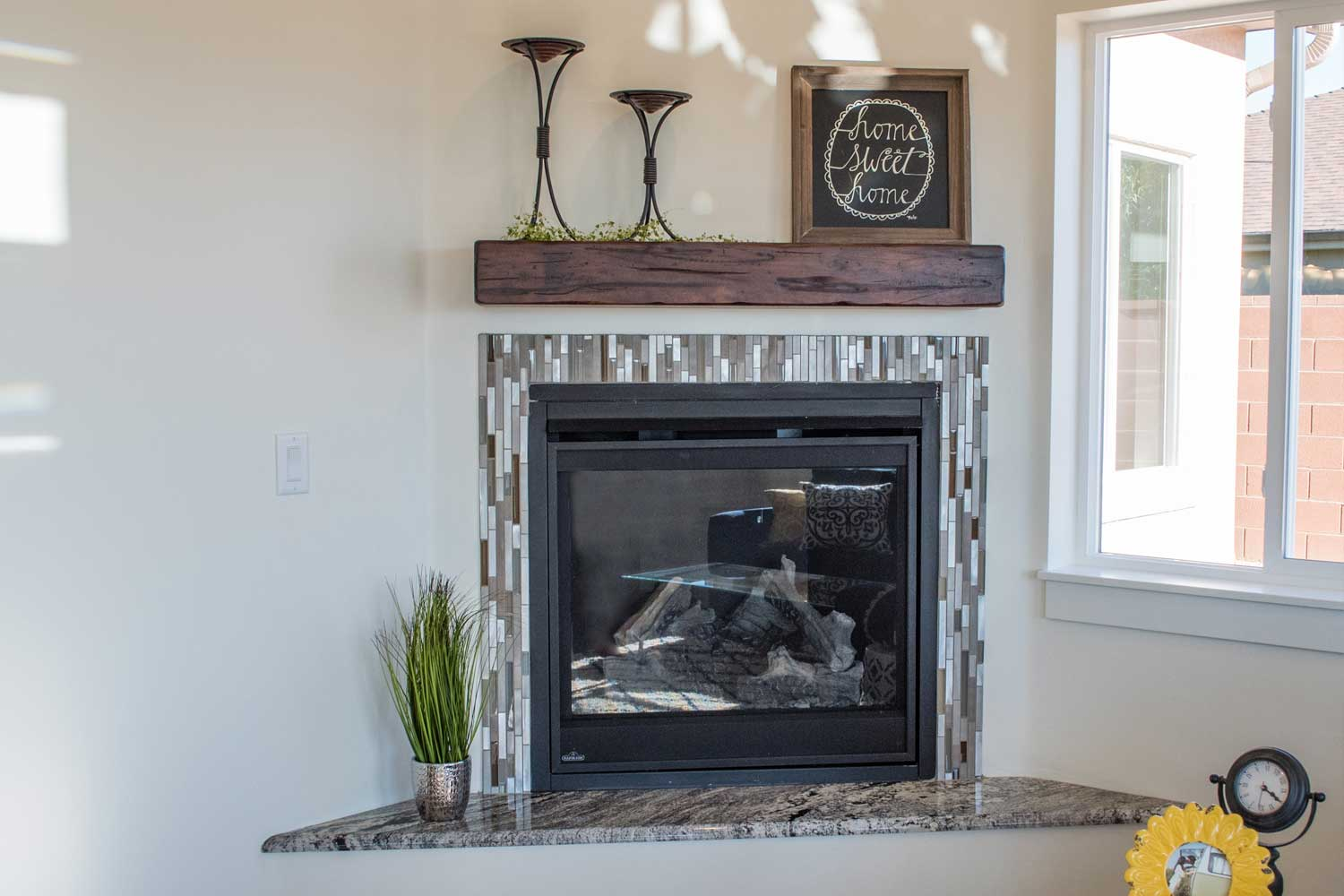 fireplace in the corner of the living room with home sweet home picture on top of the hearth