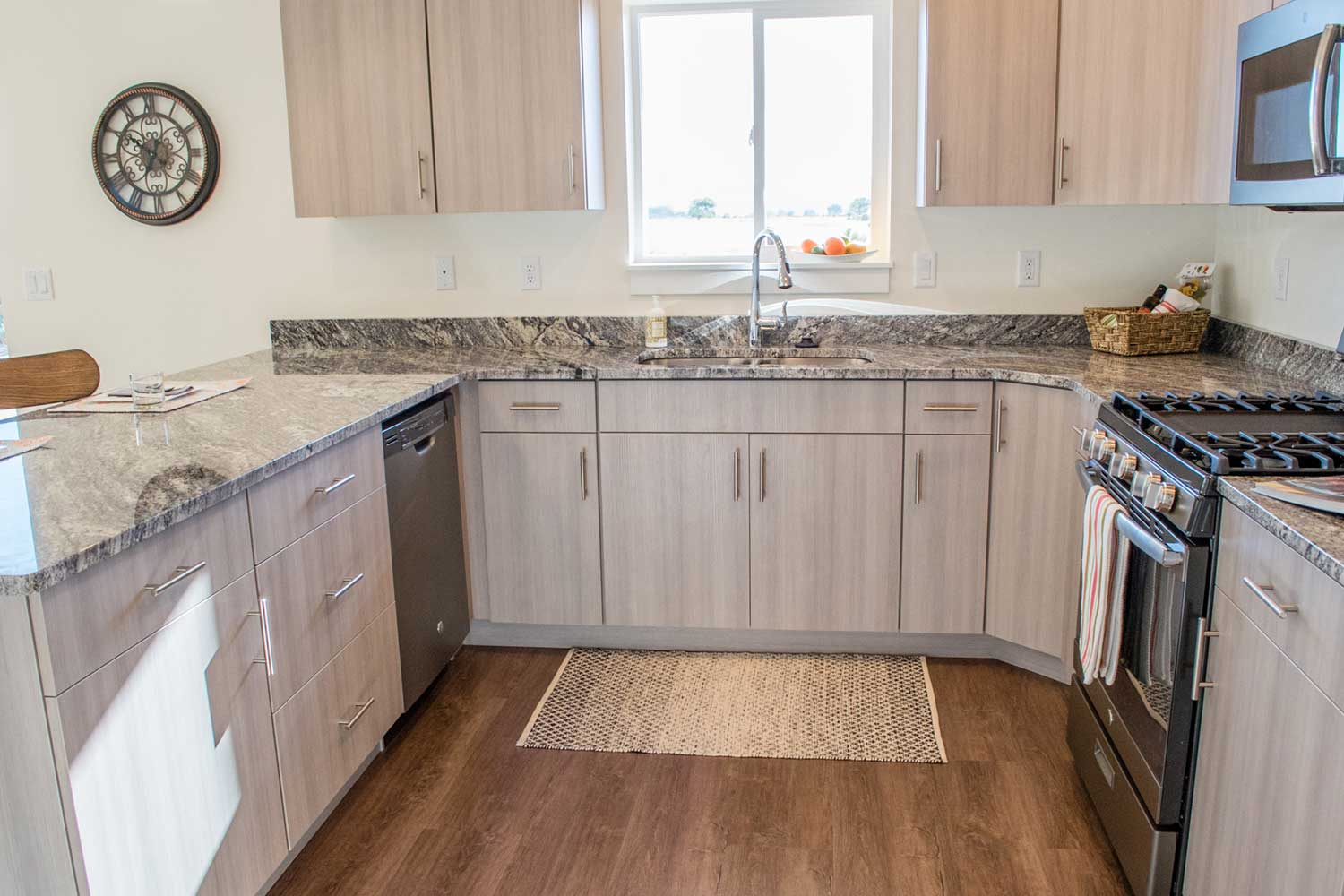 kitchen sink, granite counter tops, and light brown cabinets