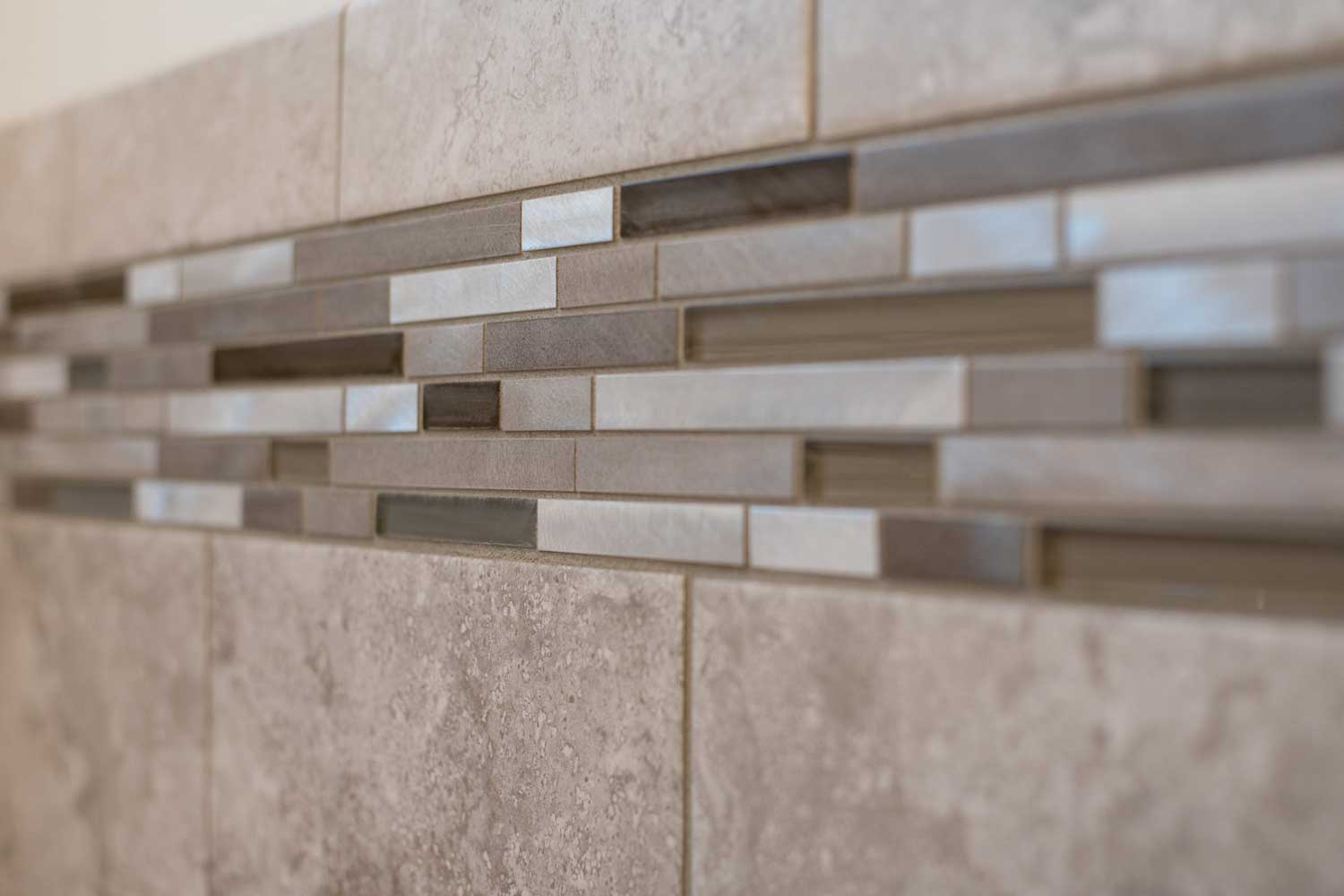 6 inch strip of shower tiles of multiple shades of brown