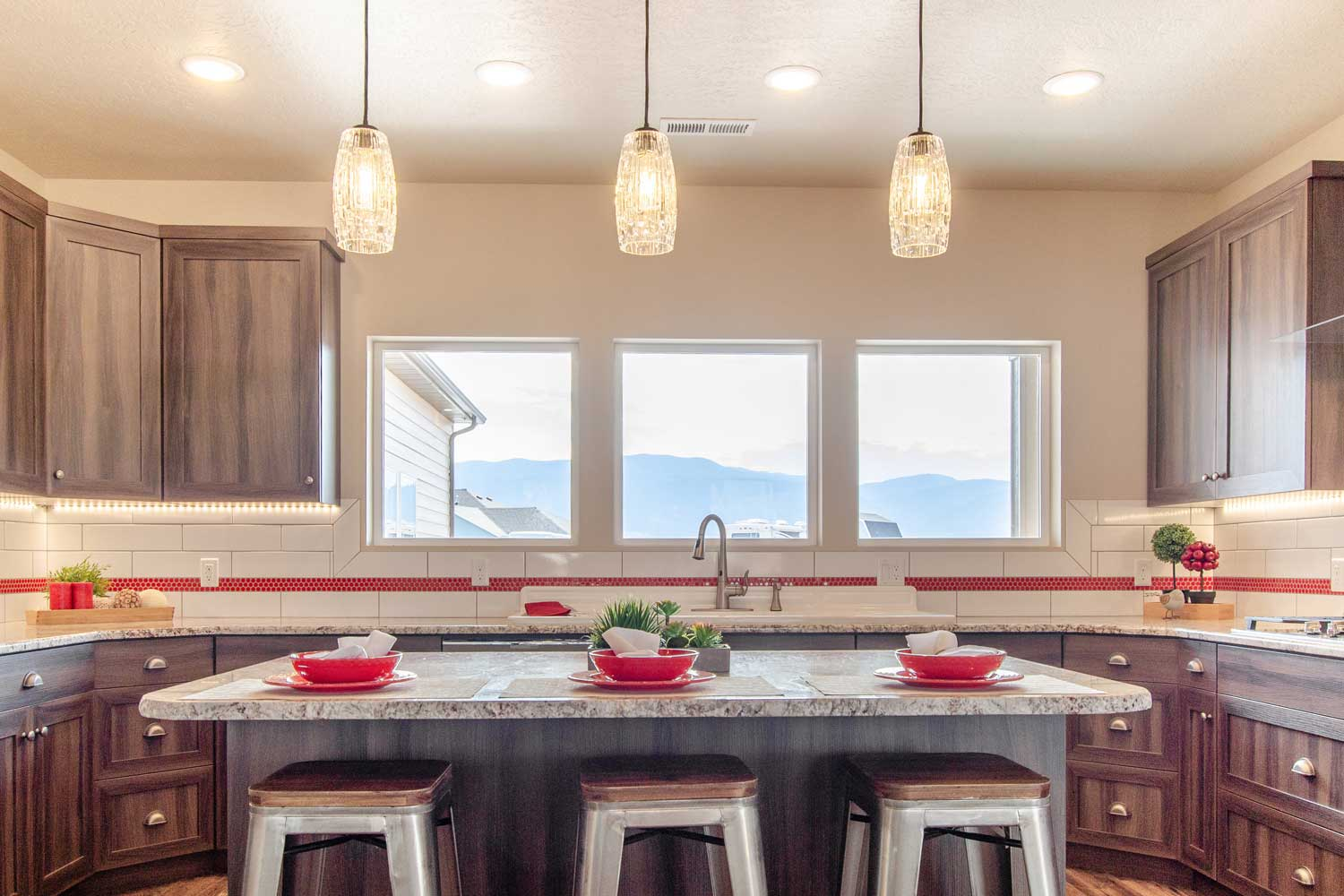 kitchen area showing tile backspace with red accents through the middle, three windows above the sink, drop ceiling lighting, three bar stools made of silver metal and wood tops
