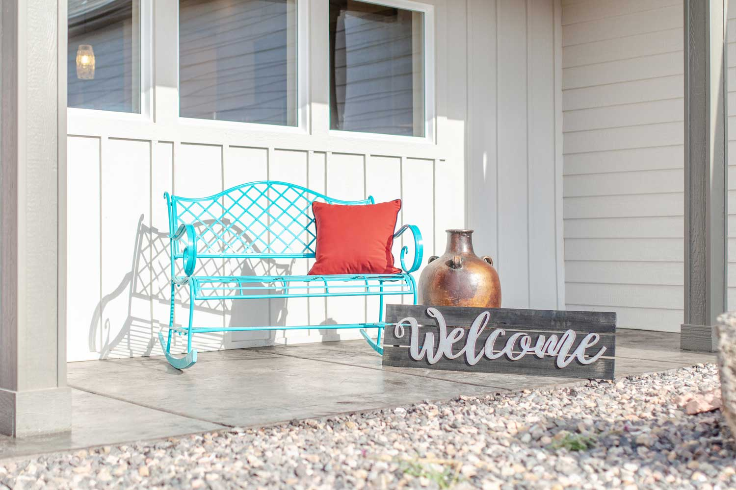 bench on the front porch with a welcome sign made of wood